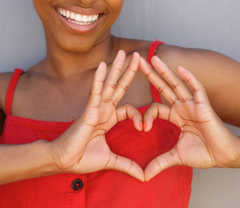 Close up portrait of young woman smiling with heart shape hand